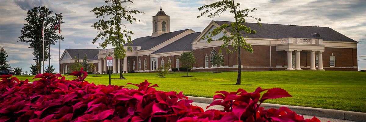 Exterior of the VOA Learning Center with red flowers in the foreground.