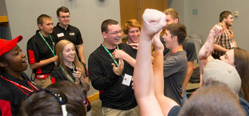 Students smiling in a circle during an icebreaker event.