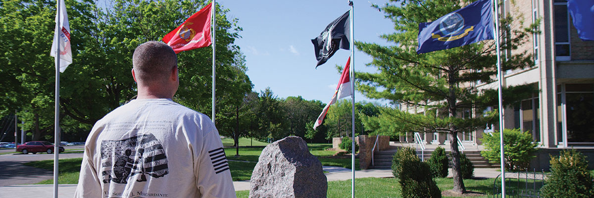 A student looking at the Veterans Memorial on the Hamilton Campus.