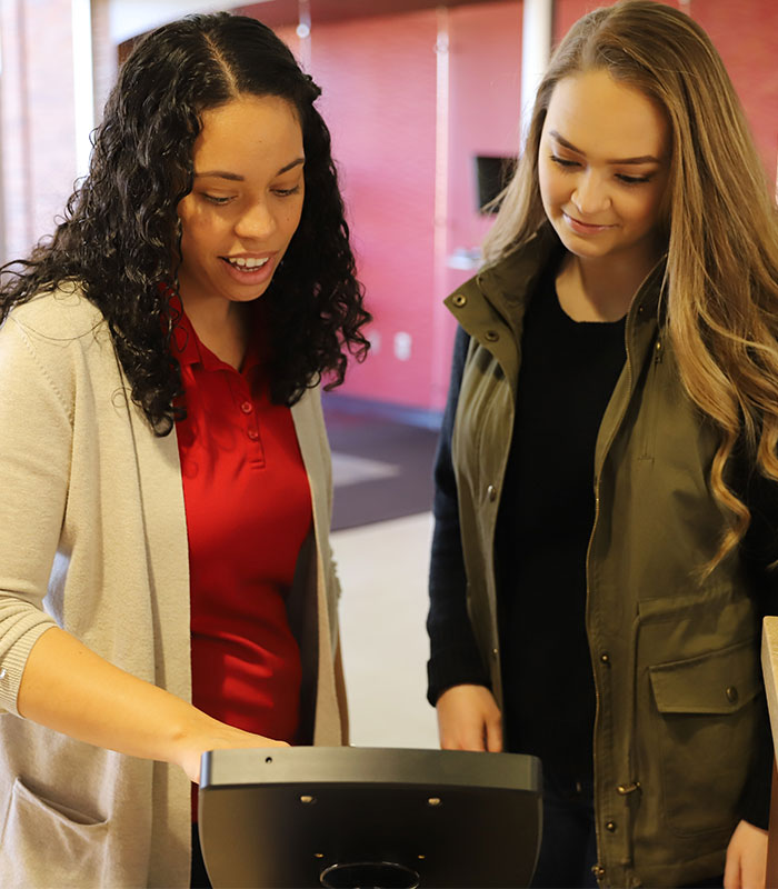A admission counselor helping a student sign into an ipad at the one stop desk.