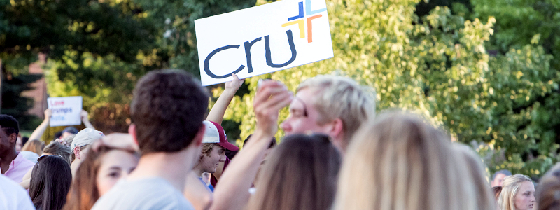 A student at Mega Fair holds up a sign advertising the Christian student group Cru