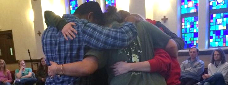 Students in a group hug during a Christian worship service