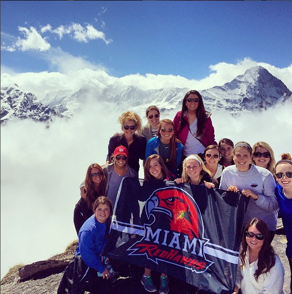 Miami students pose on top of the Swiss Alps with a Miami RedHawks flag.