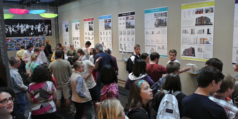 A crowd of people view a London exhibit in Cage Gallery